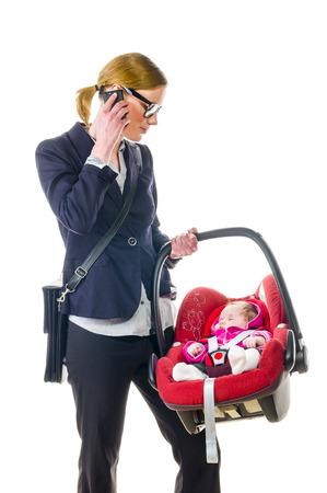 niños platicando: Mujer adulta en chaqueta oscura establece su hija recién nacida en un asiento de seguridad para automóvil, aisladas sobre un fondo blanco