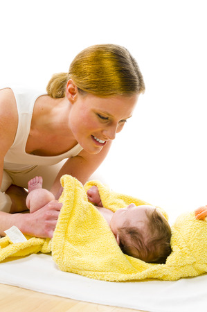 babycare: Adult mother wearing bright casual clothes, she kneels on the floor and dries the freshly bathed newborn baby with a yellow towel and smiling while doing. Isolated against white background.