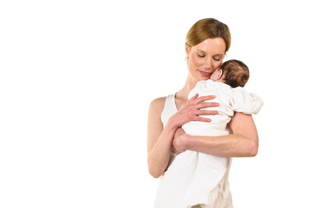 exempted female: An adult woman with white shirt also has a white-clad sweet infant tenderly in her arms, isolated against a white background  Stock Photo