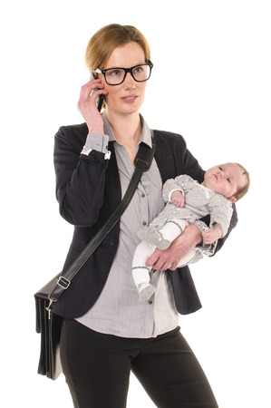 work life balance: Adult business woman Woman wearing shirt and jacket and has a baby in her arms while using a mobile phone, isolated against a white background