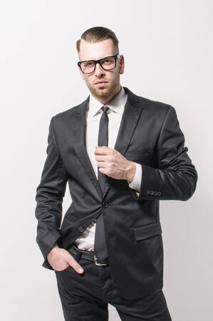 Young man with short hair and stubble wears a dark suit and a narrow tie. He has a hand casually in his pocket and the other touched his tie. photo