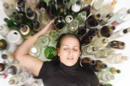 Young woman in jeans and t-shirt sitting on the floor with lots of empty beer bottles and is drunk, photographed from above, isolated against white background
