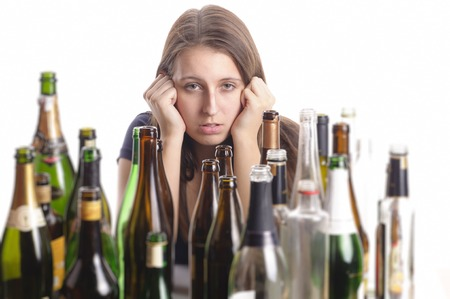 addictive drinking: A young woman with long hair brunette sits amidst empty bottles on a table and looks desperate, isolated against white background.