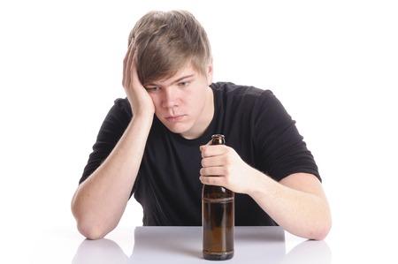 Hombre joven con el pelo rubio y corto y una camiseta negro se sienta en una mesa y sosteniendo una botella de cerveza vacía en la mano, aislado contra un fondo blanco.