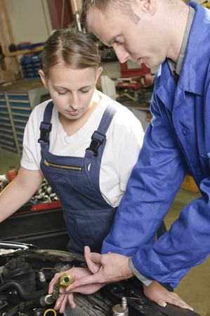 The car mechanic is with his female apprentice to a vehicle with the hood open and explain the repair.