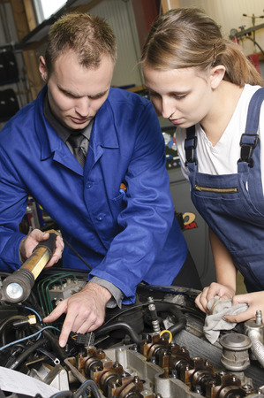 apprenticeships: The car mechanic is with his female apprentice to a vehicle with the hood open and explain the repair.