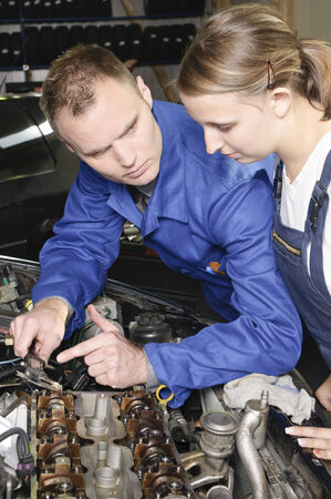 The car mechanic is with his female apprentice to a vehicle with the hood open and explain the repair. photo