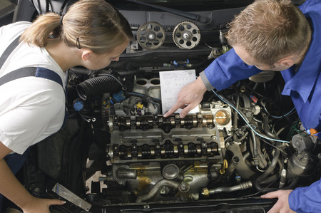 displays: The car mechanic is with his female apprentice in front of a vehicle with the hood open and displays explaining the repair.