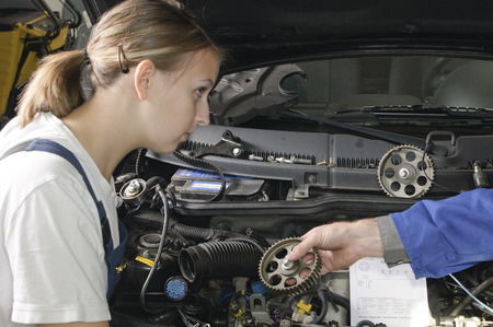 apprenticeships: Car mechanic is with a female colleague in front of a vehicle with the hood open. Both advise on repair.