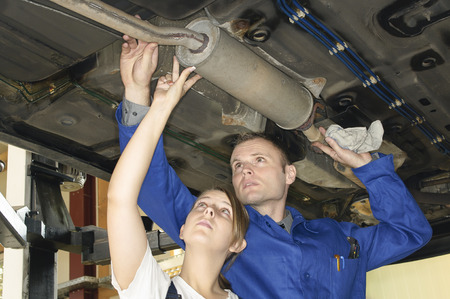 Car shows masters of the young apprentices the inspection of the exhaust system on the lower floor in the garage. Stock Photo