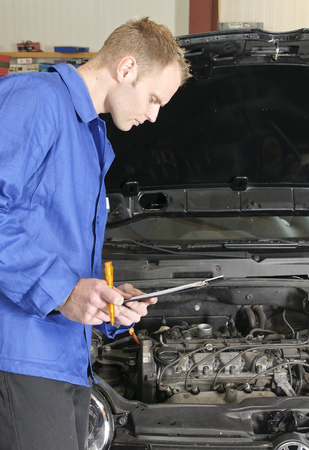 auto mechanic, mechatronic checked the engine compartment of a car in the garage photo