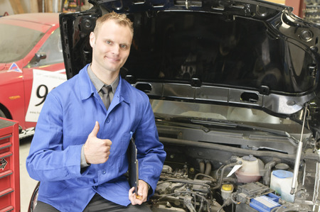 auto mechanic, mechatronic checked the engine compartment of a car in the garage, doing the thumbs up gesture Stock Photo