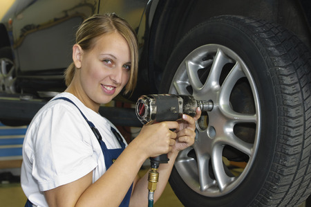 Female car mechanic in blue overalls in front of a car on the lift and impact wrench a wheel with a screw. Smiling in the camera.
