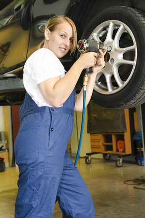 Female car mechanic in blue overalls in front of a car on the lift and impact wrench a wheel with a screw. Stock Photo