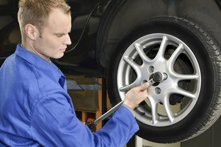 Auto mechanic in the wheel change the garage with impact wrench Stock Photo