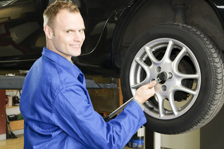 Auto mechanic in the wheel change the garage with impact wrench photo