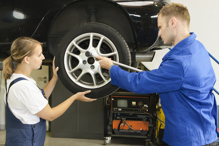 Apprentices and Cars Champion in the wheel change the garage. Stock Photo
