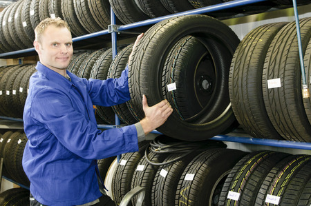 huellas de neumaticos: Mecánico de coche con un mono azul tira de un neumático de la tienda de neumáticos en el garaje