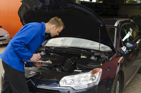 auto mechanic, mechatronic the engine compartment of a car reviewed in the garage Stock Photo