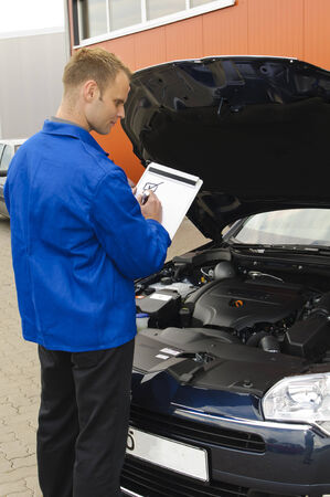 auditors: auto mechanic, mechatronic the engine compartment of a car reviewed in the garage Stock Photo