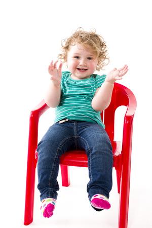 isoliert: Ein 16 Monate altes Kleinkind sitzt auf einem roten Stuhl, isoliert vor weissem Hintergrund. Stock Photo