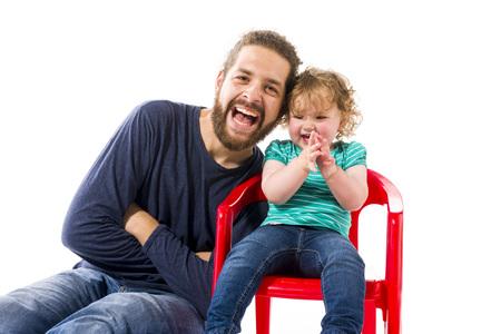 isoliert: Junger hipper Mann mit Vollbart spielt mit seiner suessen kleinen 16 Monate alten Tochter, isoliert vor weissem Hintergrund.
