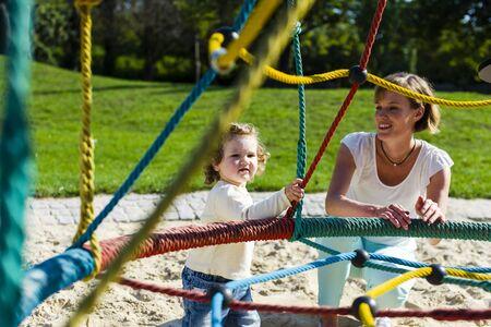 kita: Mutter und Kleinkind zusammen auf dem Spielplatz draussen.