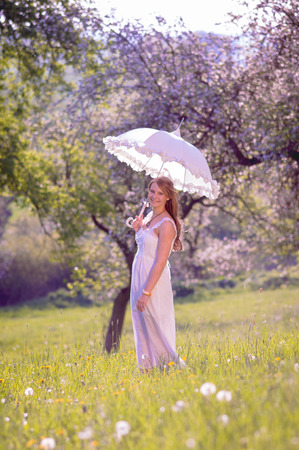 sun umbrella: A young pretty girl standing in sunset light in a meadow in front of trees and holding a sun umbrella in her hand Stock Photo