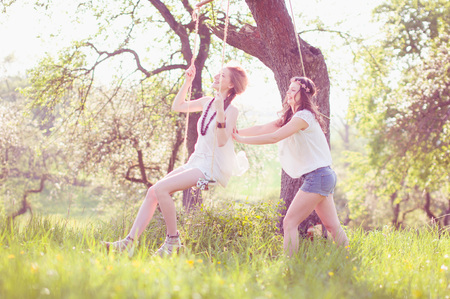 soulfulness: Two young women wear long dresses Wesse in evening light on a meadow. One sits on the swing un the other pushes her to laugh.