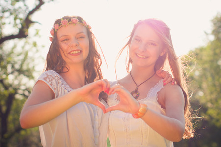 making dresses: Two young women wear long dresses Wesse in evening light on a meadow. Making with their hands, the heart symbol Stock Photo