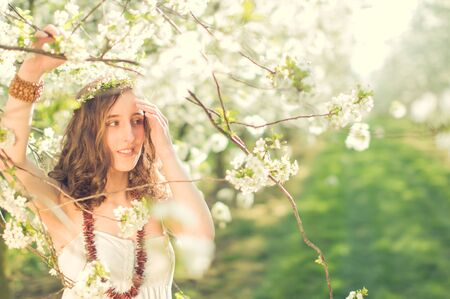 Young woman in white dress standing smiling amide colored blooming cherry trees