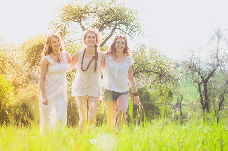 omitted: Three young girlfriends in white dresses are omitted arm in arm and laughing at the camera in a meadow in the evening light on a meadow at the edge of the forest