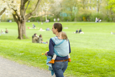 A young mother carrying her little baby in a sling on her back and walked in beautiful sunny weather by a park. The two laugh and have fun Stock Photo