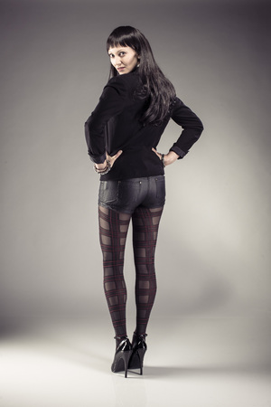 hot pants: Beautiful girl with long black hair wearing dark jacket, leather hot pants und patterned pantyhose and showing her back.