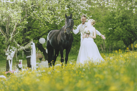 approaches: The bride in white wedding dress standing outdoors in a flowering meadow landschauft on before flowering fruit trees and holding her bridal bouquet in hand. From behind approaches the groom leading a horse to surprise her