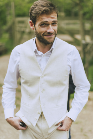grins: bearded groom is on the wedding vest with and grins at the camera