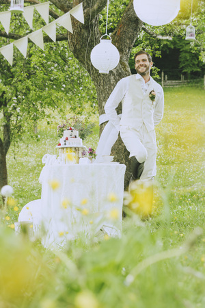jackboots: The groom wears a beige vest and is leaning against a tree in the middle of the romantic wedding decoration and smiles. Stock Photo
