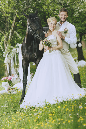 Bride and groom stand together with a magnificent black horse on a summer meadow and rays in the camera, the bride wearing her white dress and holding a bridal bouquet, the groom wearing a beige vest and brown riding boots.