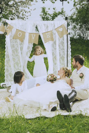 jackboots: romantic boho wedding outside in green, bride and make Groom along with their two sweet flower children a romantic picnic under the love banner
