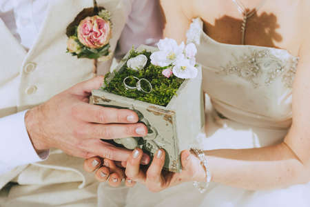 sees: detail shot of a beautifully decorated wooden box with moss and two wedding rings held by hands. In the background one sees bride and groom