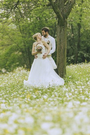jackboots: Bride and groom standing together on a gorgeous blooming summer meadow and rays in the camera, the bride wearing her white dress and holding a bridal bouquet, the groom wearing a beige vest and brown riding boots. He holds her tenderly in arm.