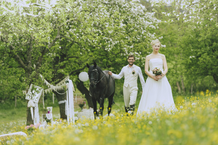jackboots: The bride in white wedding dress standing outdoors in a flowering meadow landschauft on before flowering fruit trees and holding her bridal bouquet in hand. From behind approaches the groom leading a horse to surprise her