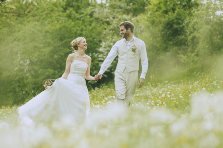 Bride and groom walking together holding hands on a gorgeous blooming summer meadow and laughing at each other. Stock Photo