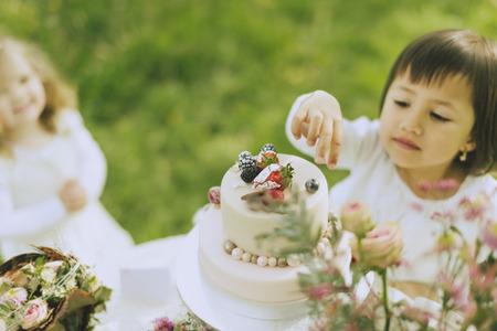 deux enfants doux peu de fleurs en jouant à l'extérieur dans la décoration de mariage et collation directement à partir du gâteau de mariage joliment décoré