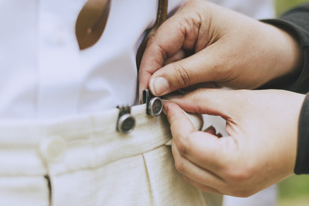 buttoned: detail of the groom as his suspenders buttoned