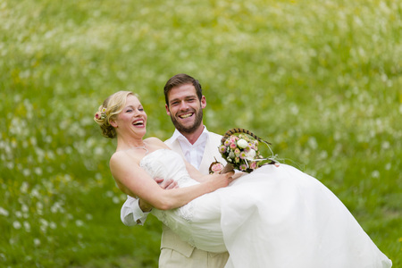 jackboots: the groom wearing his loud laughing bride the a colorful bridal bouquet in hand holds a flowering spring meadow Stock Photo