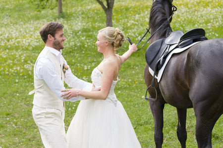 Wedding in the countryside. The bride in her white wedding dress sits on a dark horse and her bridegroom helps her dismount when the horse