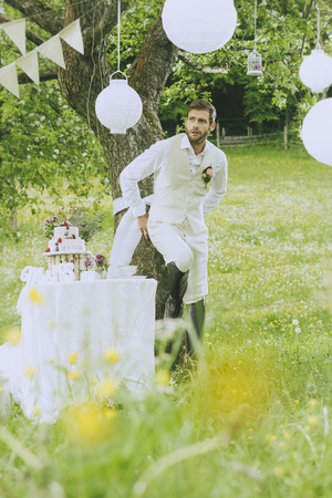 jackboots: The groom wears a beige vest and is leaning against a tree and smiles.