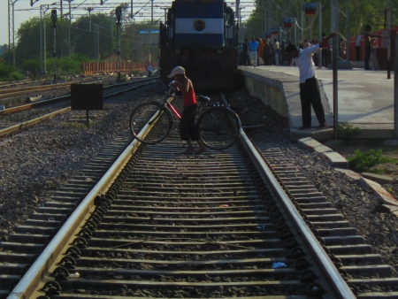 A MAN CROSSING RAILINE IN FRONT OF TRAIN ENGINE Stock Photo - 13803373