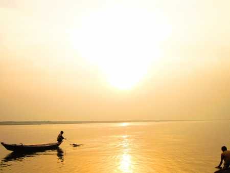 LONELY BOATMAN IN HIS BOAT AT GOLDEN SUNRISE AND A BATHER